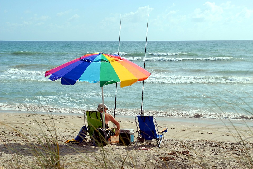Retired man sitting on a beach in Florida and fishing.