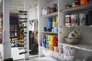A garage sale of things such as these shelved paint canisters will make your moving much easier.