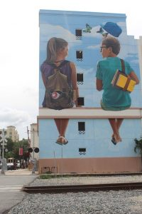 Street art in West Palm Beach picturing a boy and a girl drawn on the side of a building.