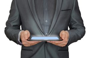 man in a suit holding tablet