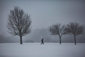 A man walking alone in a cold blizzard