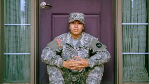 A woman soldier sitting in front of a house door
