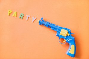 A toy pistol with the word 'party' coming out of it