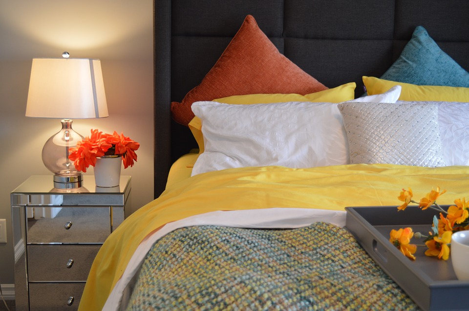 A close up of a bed with yellow bedding.