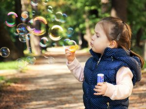 A girl blowing bubbles.