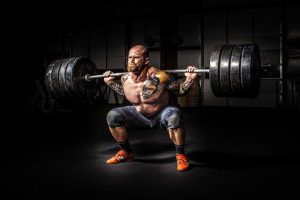 A man is trying to prepare for heavy lifting with weights.