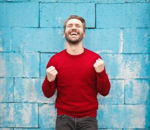 a man in red shirt in front of a blue wall