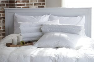 A white bed with white pillows.