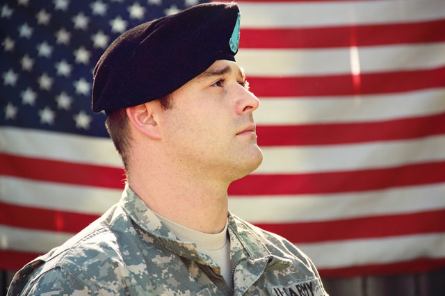 A soldier in front of a US flag in military housing