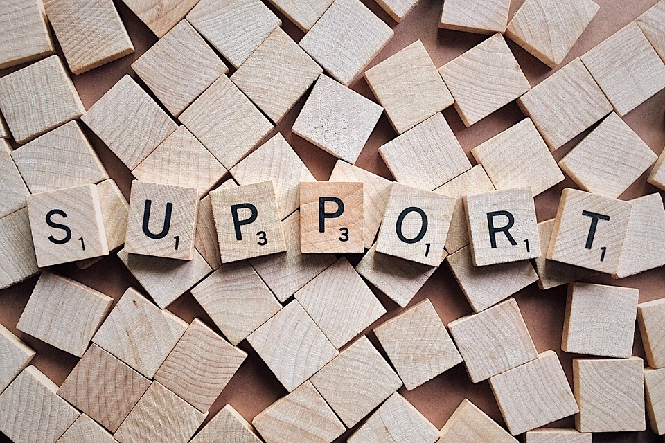 The word support spelled out with wooden cubes.