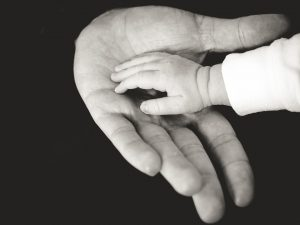 A baby's hand in a grown up person's hand.