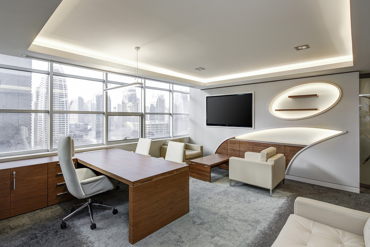 A modern white office with wooden details. Here are some things you can add to your ultimate office moving checklist.