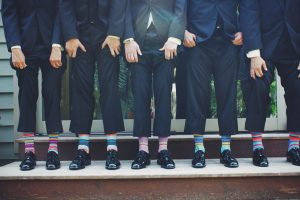 Five men in suits wearing coloful socks