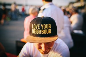 man wearing black cap with love your neighbor print during daytime