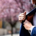 man putting wallet on suit pocket