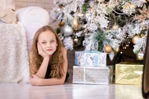 Girl next to a Christmas tree and presents