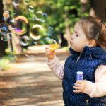 a kid blowing bubbles