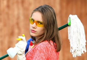 Girl with goggles, mop, and a spray bottle ready to disinfect your home before and after relocation