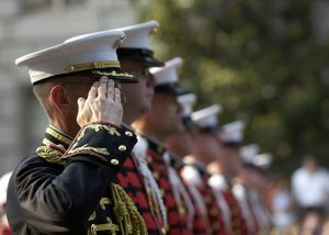 Soldiers in uniform standing in a line and saluting