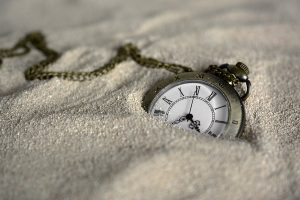 A pocket watch half-buried in sand