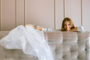 Girl uncovering plastic wrap from a bed