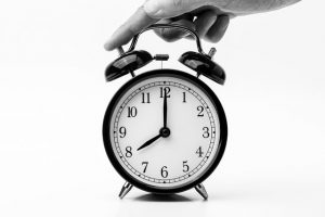 A hand stopping an alarm-clock