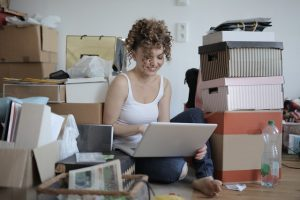 Girl packing for a move in a room full of clutter