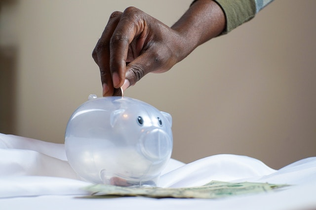 A hand putting a coin in a piggy bank because the person was able to find cheap movers in Florida