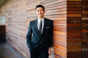 Man in a suit leaning on a wooden wall