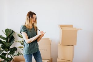 Woman writing moving boxes labels