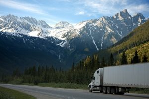 a truck on the road with a mountain range in front of it