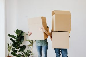 Picture of a couple with moving boxes on their heads. IF you want to put our pantry relocating tips into practice, you will have to get some moving supplies